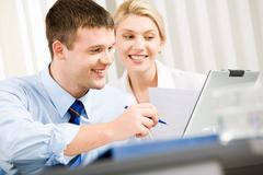 Stock Photo of smiling business man and woman  are working together in the office