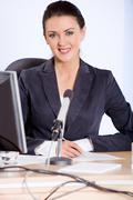 Portrait of strong woman sitting at the table and looking at camera Stock Photos