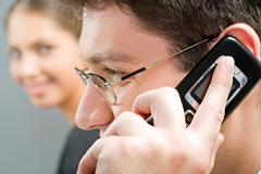 close-up of businessman with glasses calling on the phone - stock photo