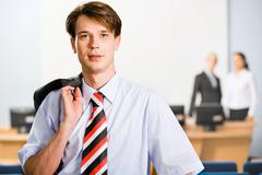 portrait of business man with jacket on his shoulder - stock photo