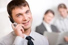 Portrait of confident boss calling by phone on the background of two businesswom Stock Photos