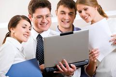 creative business team gathered together around the laptop discussing a new proj - stock photo