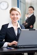 Portrait of smiling business woman in a office environment Stock Photos