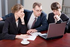 business team of three professionals looking at monitor of laptop in the office - stock photo