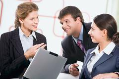 Group of three business people discussing a new plan Stock Photos