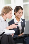 portrait of two business women looking at the monitor of laptop - stock photo