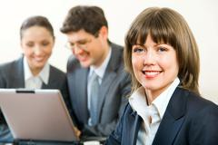 portrait of smiling businesswoman on the background of two businesspeople - stock photo