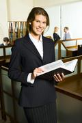 Attractive business woman is holding the book on the background of people in the Stock Photos