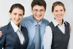 happy boss takes in his arms colleagues - stock photo