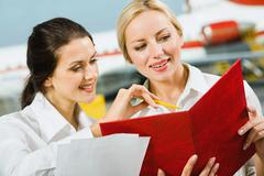 Business woman is demonstrating her colleague a plan work in an airport Stock Photos
