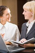 two contemporary smiling businesswomen are chatting - stock photo