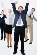 Happy business team are standing and raising hands upwards Stock Photos