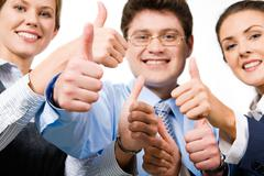 Team of three office worker's give the thumb's up sign Stock Photos