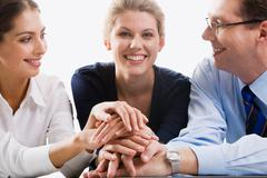 Business team putting their hands on top of each other Stock Photos