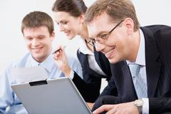 confident smiling businessman looking at the laptop on the background of  his co - stock photo