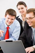 business people gathered together around the laptop - stock photo