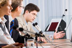 photo of business man sitting at the table and talking during a conference - stock photo