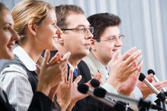 Row of successful applauding young people in office Stock Photos