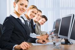 portrait of confident people sitting in a line in front of monitors and looking - stock photo