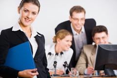 portrait of  business  female leader on the background of her working team - stock photo