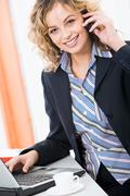confident young woman is calling by phone in the office - stock photo