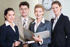 Ryhmä neljä onnistuneen ammattilaisia katsot kameraa toimistossa Kuvituskuvat