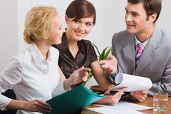 group of three young business people are discussing new working plan in the offi - stock photo