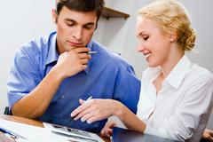 Charming assistant is demonstrating important document to her boss in the office Stock Photos