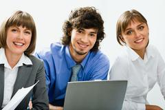 Portrait of three smiling business people looking at camera Stock Photos