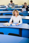 portrait of smart woman sitting at the blue table with books on it in the classr - stock photo