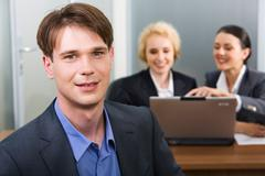 portrait of handsome business man on the background of two business women - stock photo