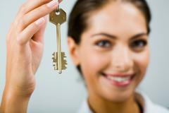 smiling business woman is holding the key - stock photo