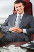 Portrait of business man sitting in the armchair in his office in a relaxed pose Stock Photos