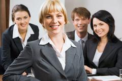 Female leader on the background of  her business team Stock Photos