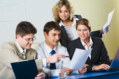 Group of people sitting at a blue table and discussing business questions Stock Photos