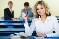 portrait of smart student holding the pen and sitting at the table with books - stock photo