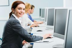 portrait of busy woman sitting at the computer table and touching computer mouse - stock photo