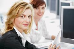 two wonderful smiling female students is sitting at the table in the classroom - stock photo