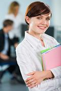 Wonderful smiling student is holding the two books in the classroom Stock Photos