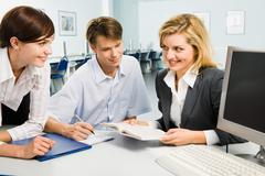 Group of three young business people are discussing new teaching material in the Stock Photos