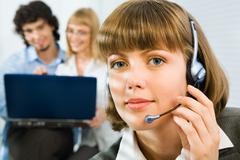 Friendly telephone operator is holding headset on the  background of two  co-wor Stock Photos