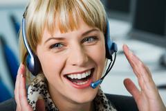 Portrait of laughing woman with headset in the office Stock Photos