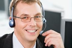 portrait of  smiling negotiator with glasses and headset - stock photo