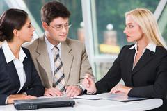 Three young professionals gathered together discussing important business plan i Stock Photos