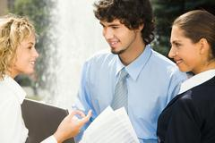 Group of three people talking  about their business examination Stock Photos