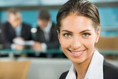 close-up of beautiful woman smiling on the background of two businesspeople in a - stock photo