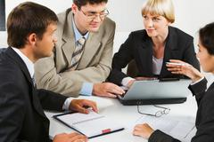 team of four business people sitting at the table with laptop, notepad, papers, - stock photo