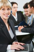 successful woman with headset smiling on the background of three business people - stock photo