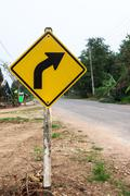curved road traffic sign on the road at country side - stock photo