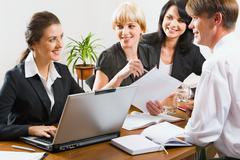 Ryhmä menestyksekkäitä liikemiehiä istuu pöydässä kannettava tietokone, muistikirjat, Kuvituskuvat